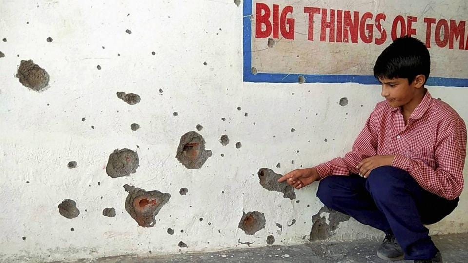 A student shows bullet marks on the wall of his schhol building after firing from the Pakistan side, near the Line of Control in Poonch district on Tuesday.