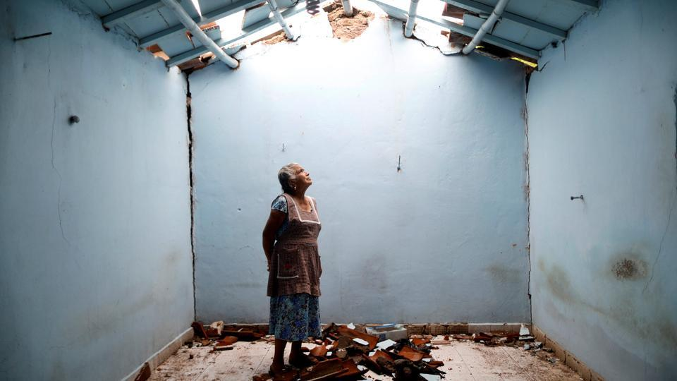 Tomasa Mozo, 69, a housewife, looks up at the roof inside the ruins of her house after the earthquake that struck Mexico in September. Her house was badly damaged but with the help of family Mozo rescued some furniture. She lives in another room of her house and hopes to repair the damage as soon as possible. 'I'm afraid to go out, I can not sleep,' Mozo said. (Edgard Garrido / REUTERS)