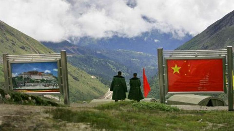 Chinese army officers oversee preparations as they stand between pictures of the Patola Palace, left, and the Chinese flag, on the Chinese side of the international border at Nathula Pass, in Sikkim, in July  2006.
