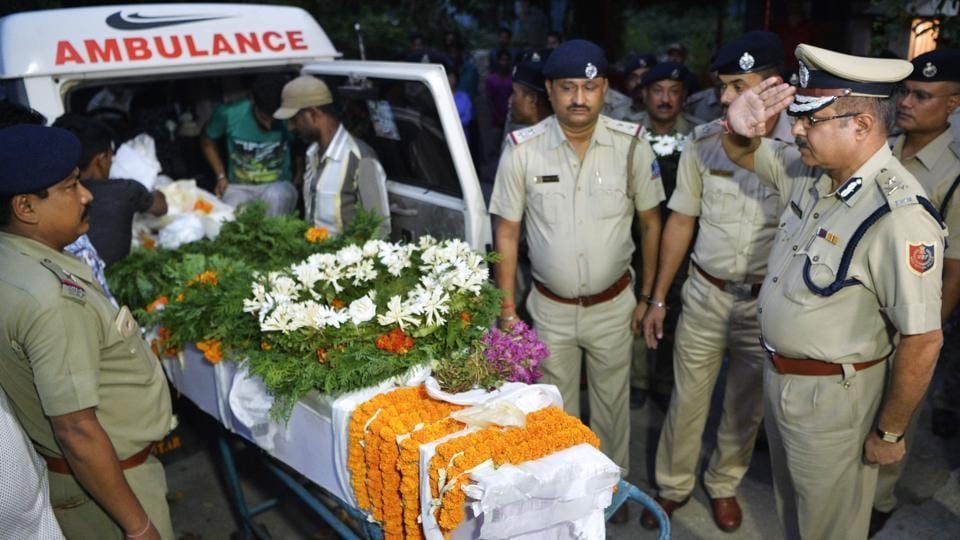 Police personnel pay homage to slain police officer Amitava Malik, who was killed during a gunfight between West Bengal police and Gorkha Janamukti Morcha (GJM) supporters in Darjeeling, in Siliguri on October 13, 2017.
