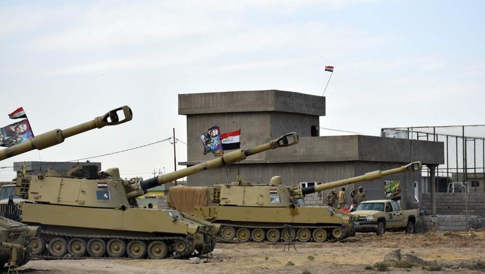 Iraqi army vehicles are seen parked near a former Kurdish military position on October 13, 2017 in the northern Iraqi town of Tuz Khurmatu, near Iraq's oil-rich multi-ethnic province of Kirkuk.