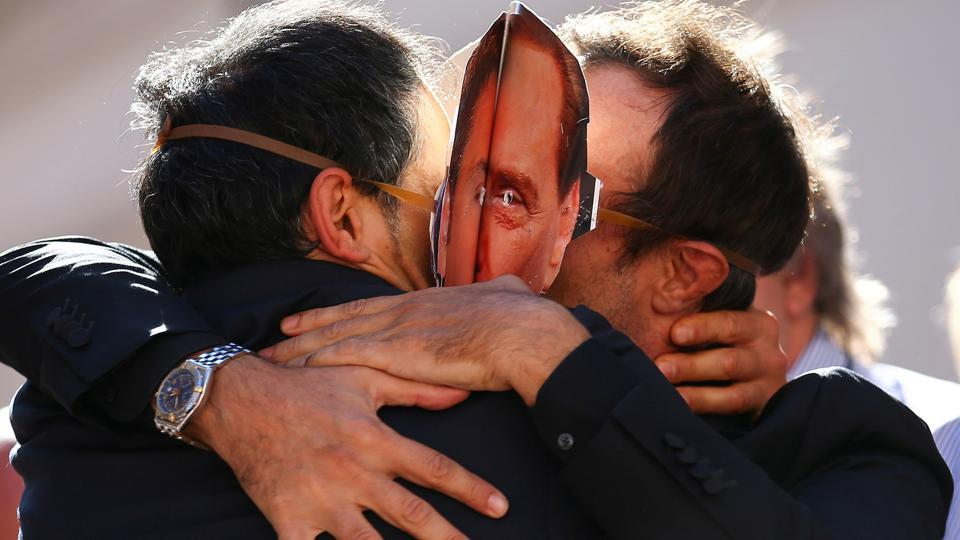 5-Star Movement supporters kiss each other as they wear masks depicting former Italian Prime Ministers Silvio Berlusconi (R) and Matteo Renzi during a protest in front of Montecitorio government palace in Rome, Italy, October 11, 2017.  (Alessandro Bianchi / REUTERS)