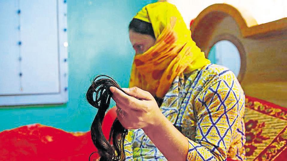 A Kashmiri woman shows her braid, which was cut in central Batamalloo area of Srinagar on October 09.