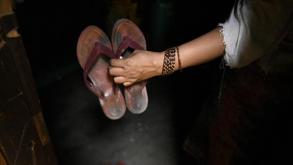 Sabera Khatun shows a pair of slippers, which she brought with her when she fled her home in Myanmar and came to India. (Burhaan Kinu / HT PHOTO)