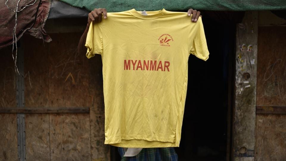 A man holds up his son's football club t-shirt in a Rohingya refugee camp in New Delhi. The club, called 'Rohingya Shining Stars', has seventeen boys from the camp who love football. As the refugees' fate in India hangs uncertain, they will hope for some relief as the Supreme Court hears their case today on the Indian government's stand to deport them.  (Burhaan Kinu / HT PHOTO)