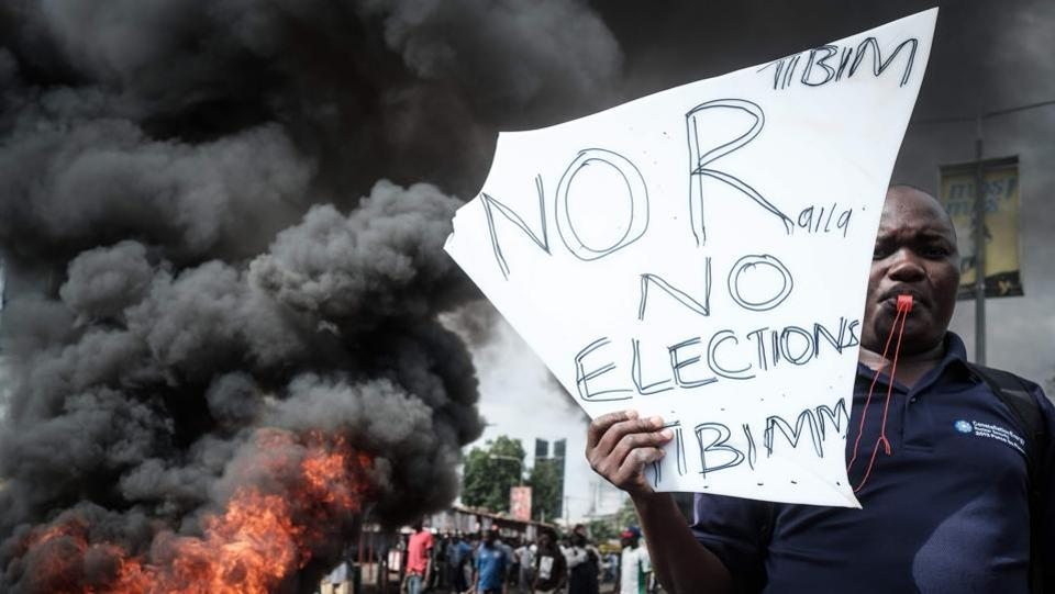 An opposition supporter holds a placard during their protest against Independent Electoral and Boundaries Commission (IEBC) officials over claims of bungling the August presidential vote, which was nullified by the Supreme Court, in Kisumu, Kenya, on October 11, 2017. (Yasuyoshi Chiba / AFP)