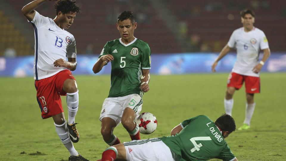 Mexico's Luis Olivas (on the ground)and Raul Sandoval fight for the ball with Chile's Yerco Oyanedel (left)during their FIFA U-17 World Cup Group F football match in Guwahati on Saturday. Get highlights of the Mexico vs Chile match here.