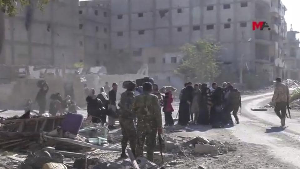 This frame grab from a video provided on October 13 by Turkey-based Kurdish Mezopotamya agency media outlet that is consistent with independent AP reporting, shows US-backed Syrian Democratic Forces (SDF) fighters, stand around Syrian civilians who fled from the areas that still controlled by the Islamic State militants, in Raqqa, Syria.