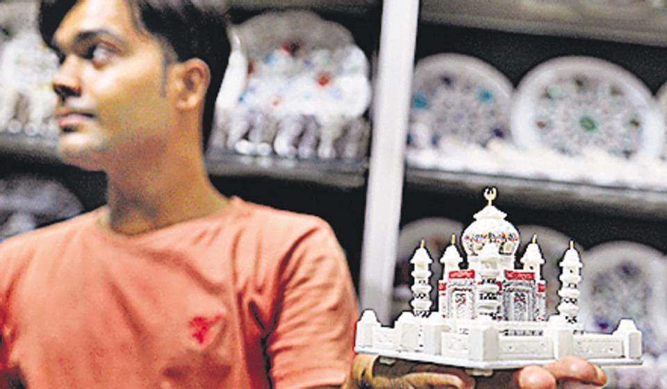 A shopkeeper in Agra shows off a miniature version of the Taj. Miniatures of the monument are popular picks by tourists to the heritage site.
