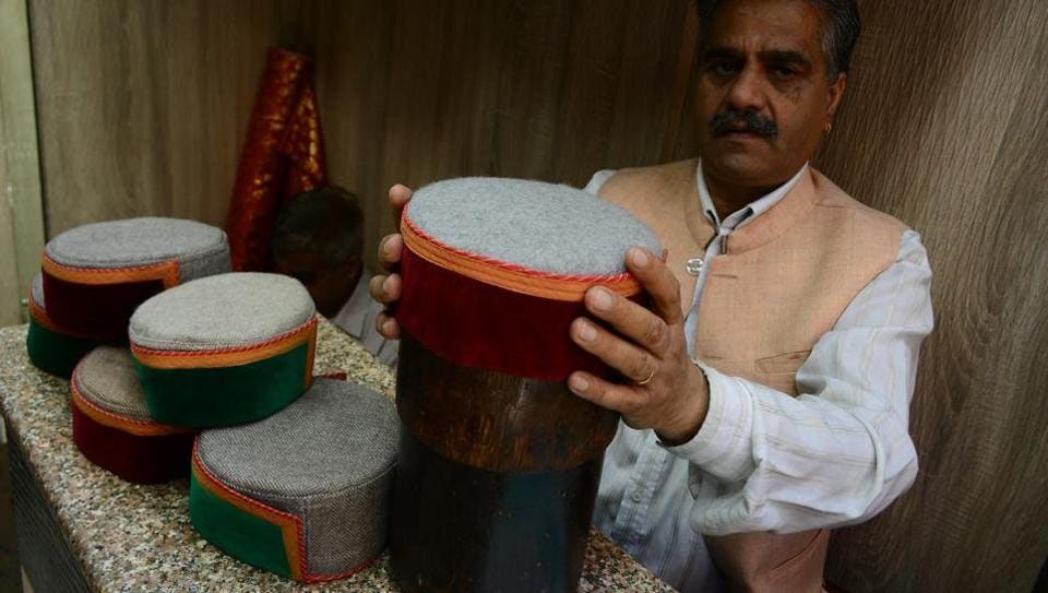 A shopkeeper showing traditional Himachali caps in a shop at Lower Bazaar, in Shimla.