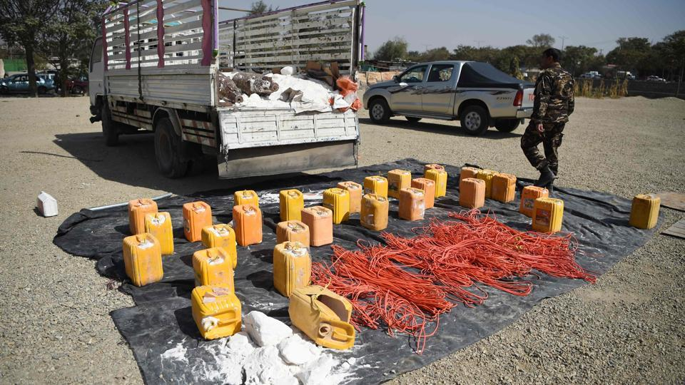 An Afghan security force personnel walks next to containers filled with explosive material after presenting it to the media at the National Directorate of Security (NDS) headquarters in Kabul on October 15, 2017.