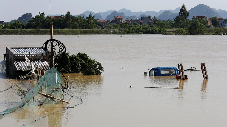 A submerged truck and houses are seen at a flooded village after a heavy rainfall caused by a tropical depression in Ninh Binh province, Vietnam October 14, 2017.