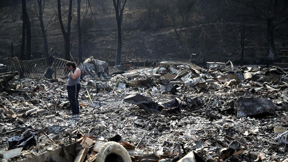 Heather Tiffee wipes her eyes as she looks through the remains of her parents' home after it was destroyed by the Atlas Fire on October 13, 2017 in Napa, California.  (AFP Photo)