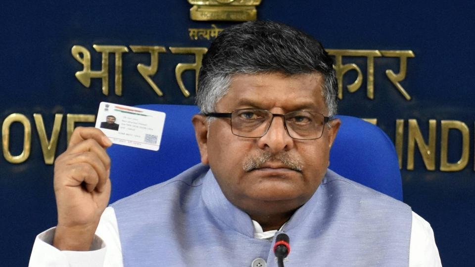 Telecom minister Ravi Shankar Prasad shows his Aadhaar card at a press conference.
