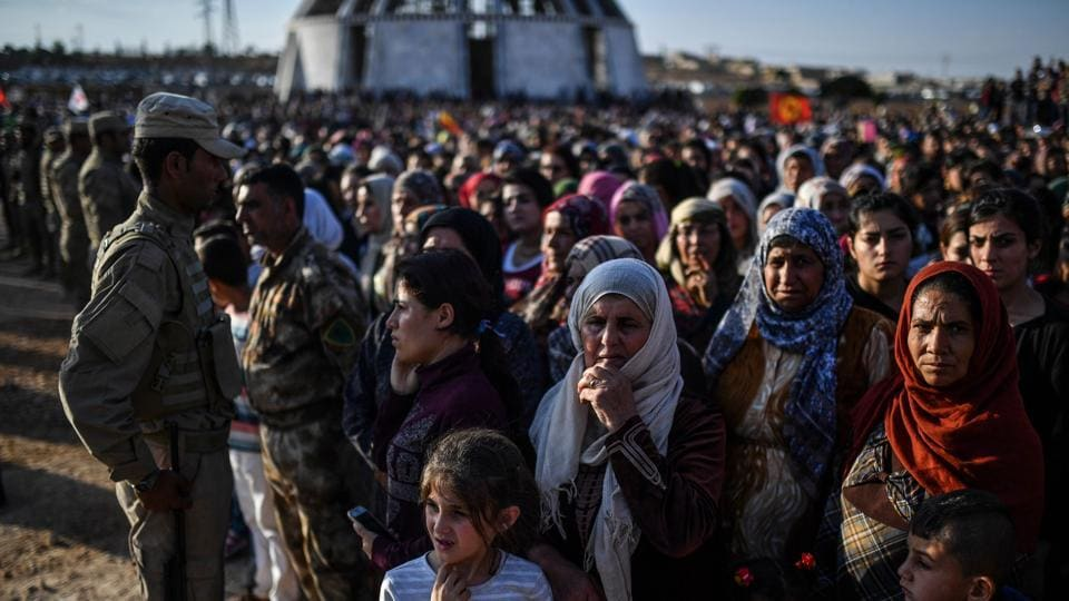 A picture taken on October 14, 2017 in the Kurdish town of Kobane in northern Syria shows people gathering for the funeral of a Kurdish fighter, who was killed in clashes against Islamic State (IS) group fighters in the city of Deir Ezzor.