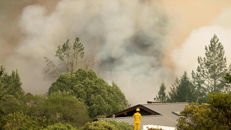 A firefighter watches smoke billow as flames approach a residential area in Sonoma in California. (AFP Photo)