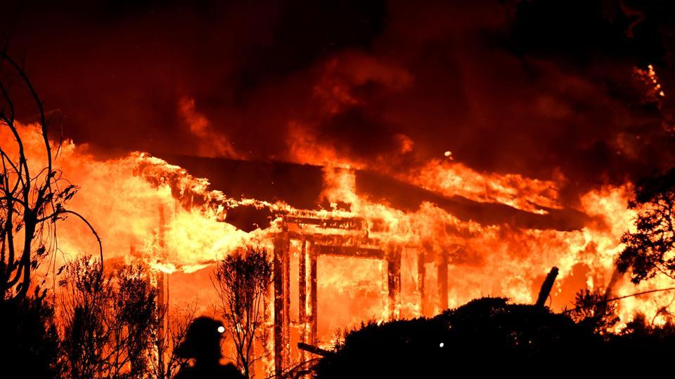 Firefighters assess the scene as a house burns in the Napa wine region of California  as multiple wind-driven fires continue to ravage the area burning structures and causing widespread evacuations.  (AFP Photo)