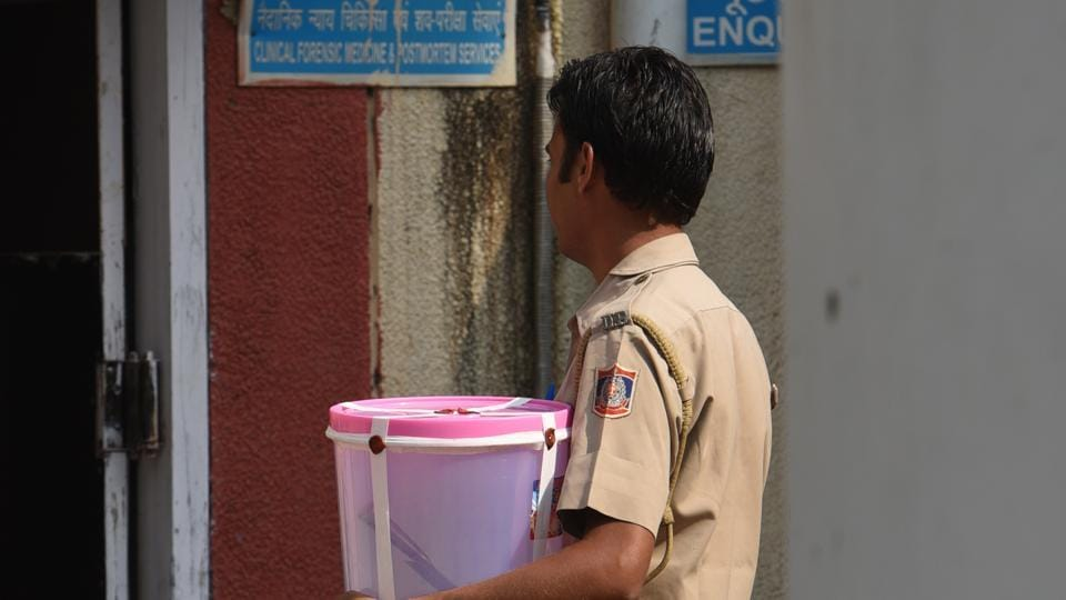 A Delhi Police officer carries the meat cleaver that was apparently used to kill 30-year-old Vipin Joshi and chop his body iN Saket.
