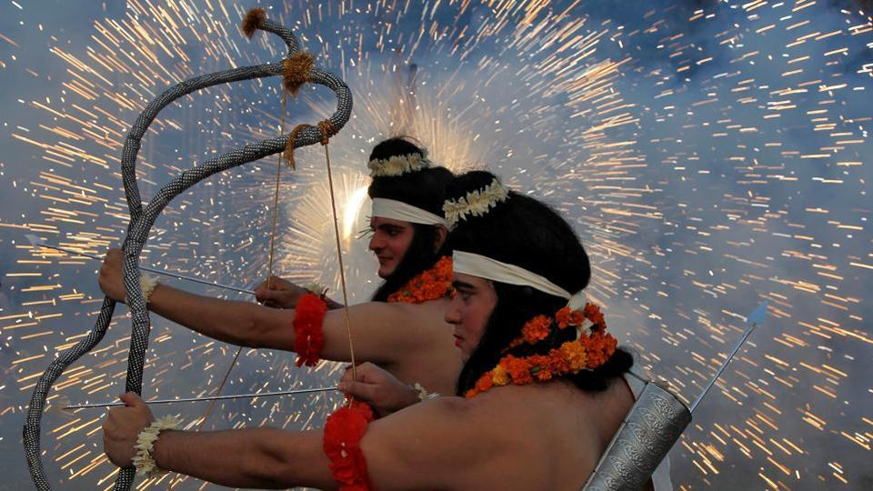 Artists dressed as Hindu gods Ram and Laxman act as fireworks explode during Dussehra celebrations.
