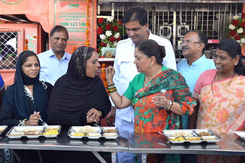 Chief minister Vasundhara Raje serves food to a woman during launch of Annpurna kitchen in Ajmer on Monday.