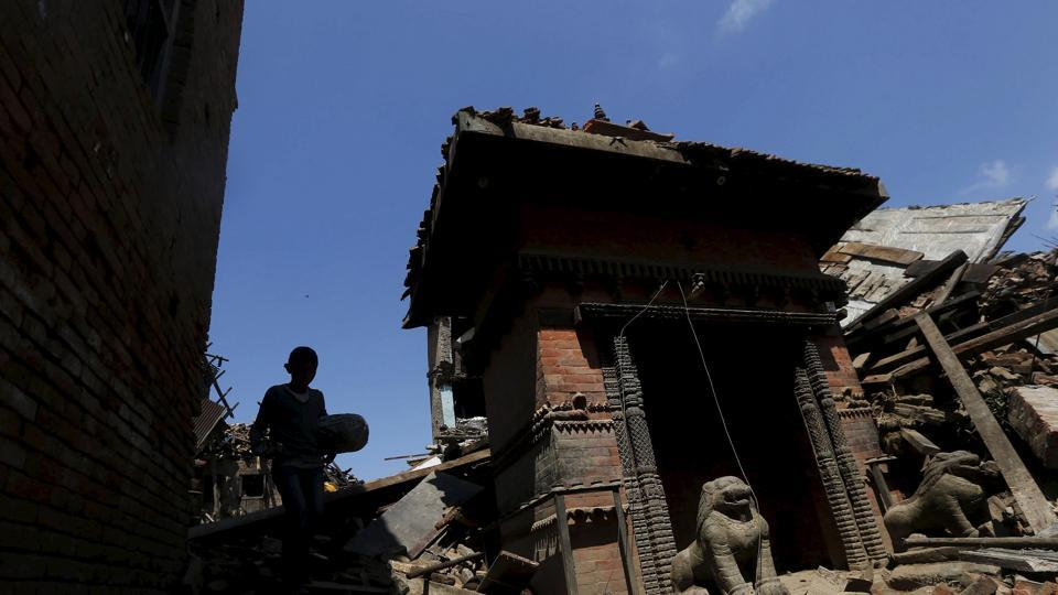 A boy carrying a bolster walks past a damaged temple after Saturday's earthquake in Bhaktapur, Nepal April 27, 2015.