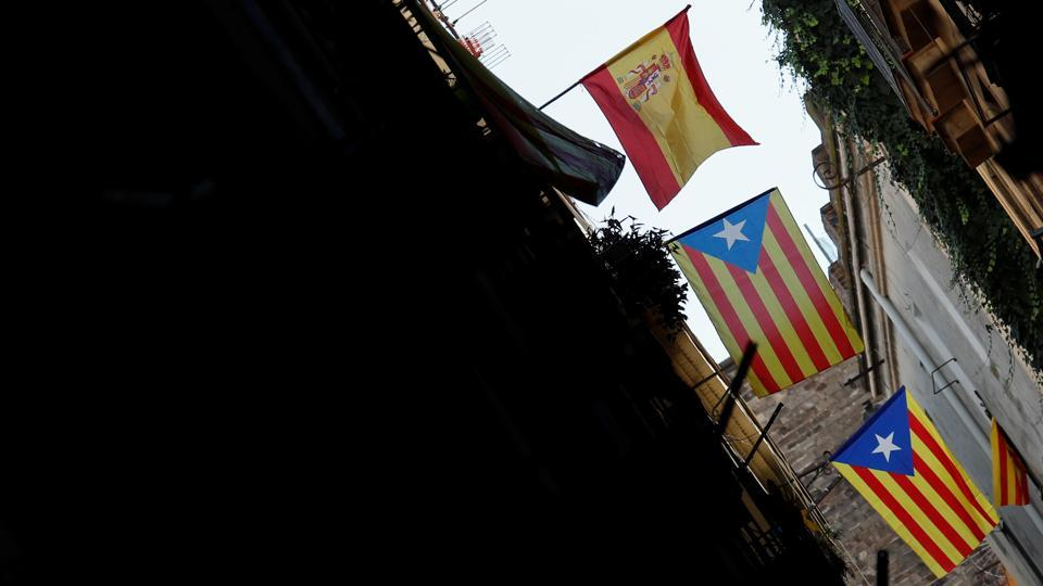 Esteladas (Catalan separatist flags) and a Spanish flag (L) hang from balconies of a building in Barcelona, Spain, October 16, 2017.