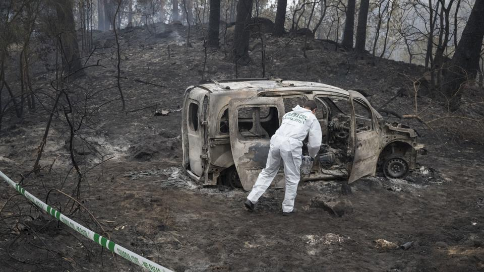A Police scientist inspects the remains of the car where two women died after a wild fire in Pontevedra, in the northwestern Spanish region of Galicia, Spain, Monday, Oct. 16, 2017.