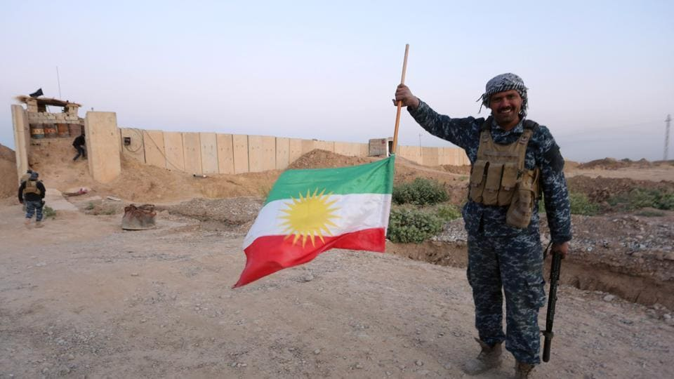 A member of Iraqi federal forces holds the Kurdish flag upside down after Iraq's central government forces seized Kurdish positions in Kirkuk, Iraq October 16, 2017.