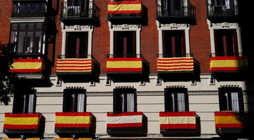 Spanish and Catalan flags are hung from the balconies of an apartment building in Madrid.