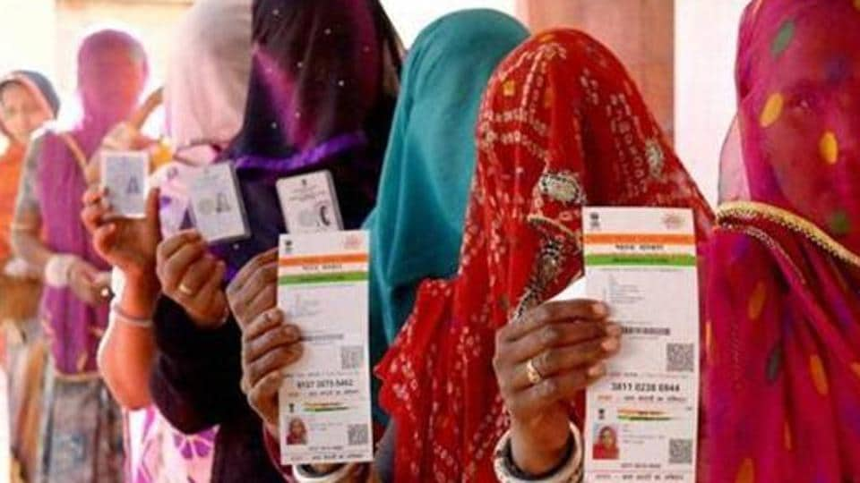 Rajasthani women show their Aadhaar cards while standing in a queue to vote for Ajmer District Panchayat elections in 2016.