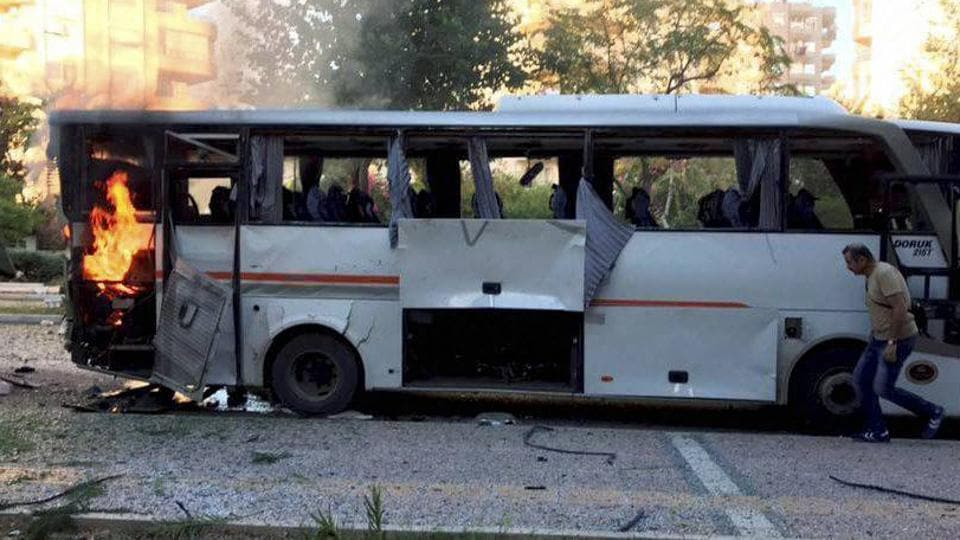 A bus carrying police officers still burning shortly after a bomb went off as the bus was passing by in Mersin in southern Turkey, Tuesday, Oct. 17, 2017.