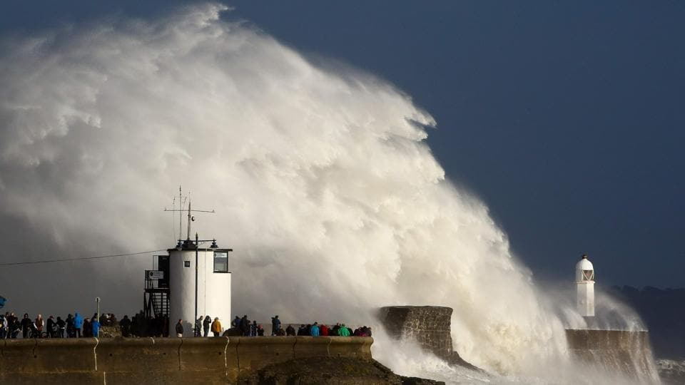 Huge waves strike the harbor wall and lighthouse at Porthcawl, South Wales, on October 16, 2017 as Storm Ophelia, downgraded from a hurricane arrives in the UK and Ireland. Ophelia ramming Ireland on Monday left three people dead, 330,000 homes and businesses without power, the shutting of schools and the grounding of planes in the country. (Geoff Caddick / AFP)