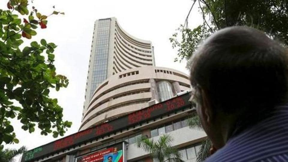 File photo of a man looks at a screen across a road displaying the Sensex on the facade of the Bombay Stock Exchange (BSE) building in Mumbai, India.