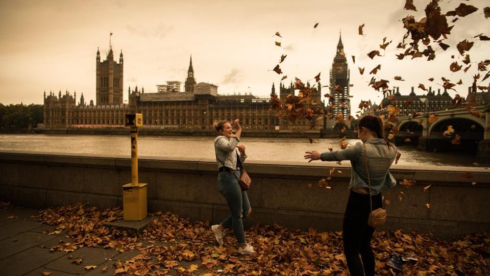 Girls throw leaves opposite the Houses of Parliament during a reddish sky caused by remnants of Ophelia on October 16, 2017 in London. This movement of air from the continent also brought in warmer temperatures, including highs of up to 22 degrees Celsius in parts of southern England, including London. (Carl Court / Getty Images)
