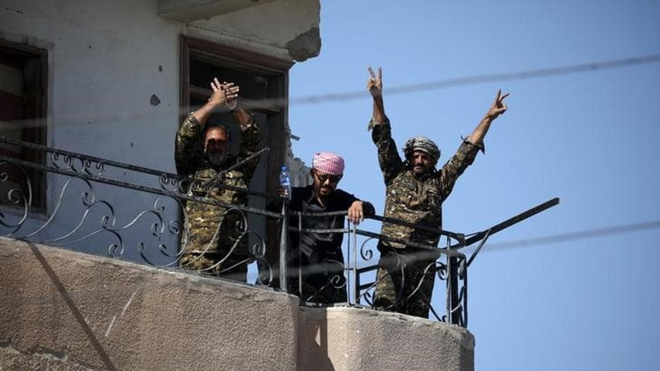 Fighters of Syrian Democratic Forces gesture the