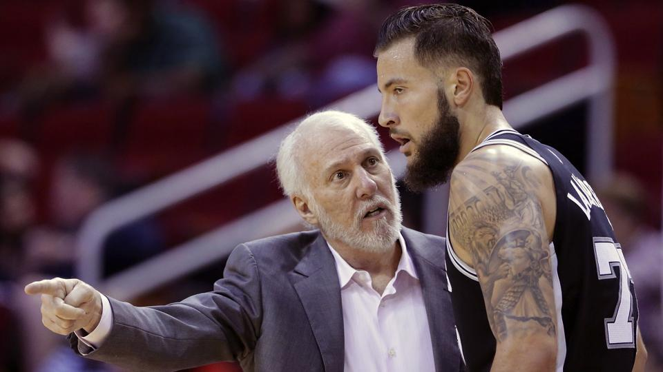 San Antonio Spurs head coach Gregg Popovich talks with Spurs forward Joffrey Lauvergne (77) in the second half of an NBA pre-season basketball game against the Houston Rockets Friday, Oct. 13, 2017, in Houston.