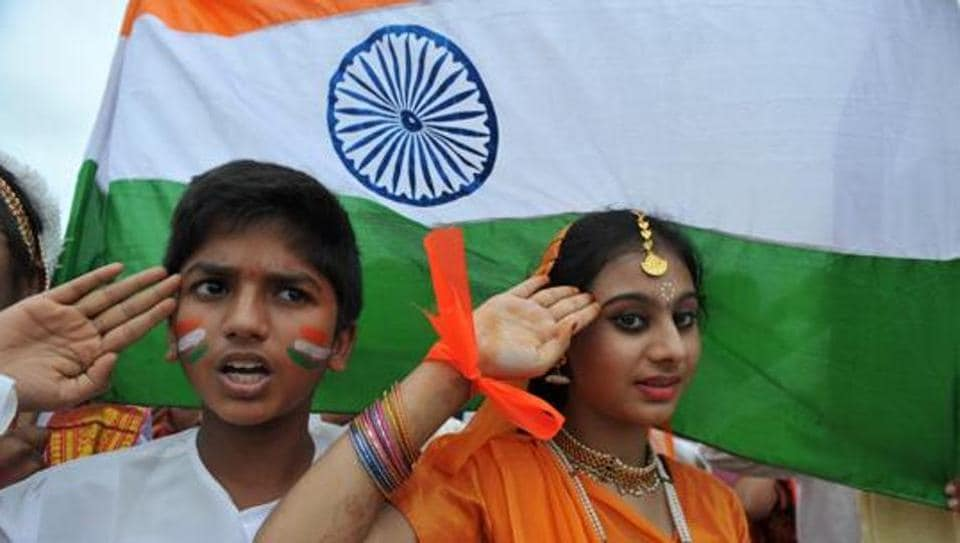 School children salute as they stand to attention and sing the national anthem Jana Gana Mana at a school in Hyderabad.