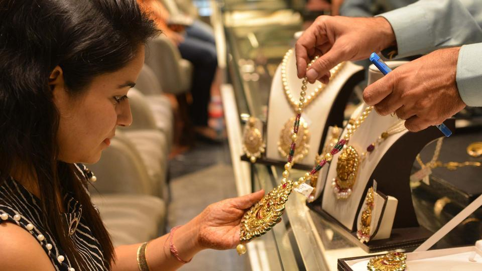 An shopper looks for gold jewellery and ornaments during Dhanteras at a jewellery store in Amritsar on October 17, 2017.