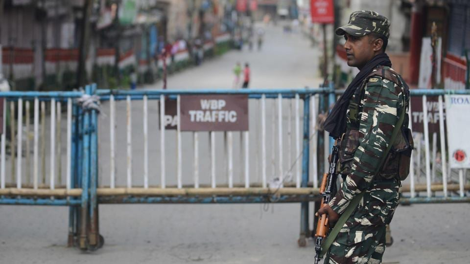 A paramilitary forces soldier stands guard along a road in Kalimpong.