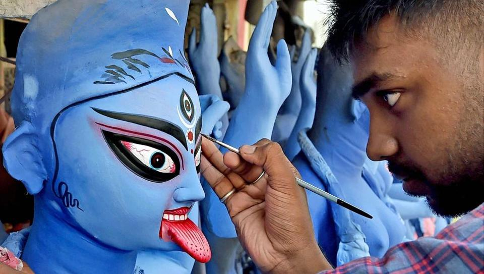 An artist gives finishing touches to a Goddess Kali idol ahead of Kali Puja. About 10,000 people, comprising Hindus and Muslims, in three villages in Assam's Milan Chowk, celebrate Kali Puja together.