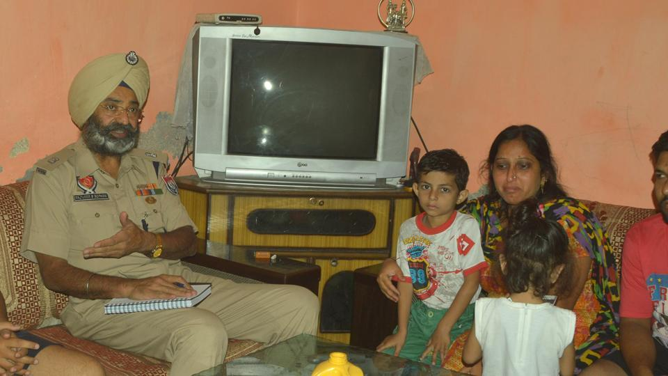 A police officer interacting with the family members of local RSS leader Ravinder Gosai who was shot dead in Ludhiana on Tuesday.