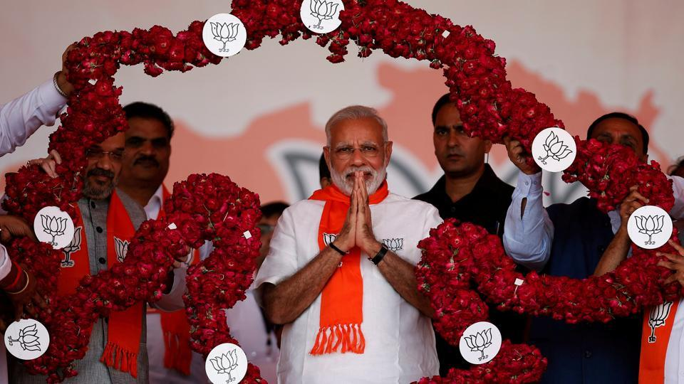 Prime Minister Narendra Modi is garlanded by supporters during a public rally at Bhaat village on the outskirts of Ahmedabad on October 16, 2017.