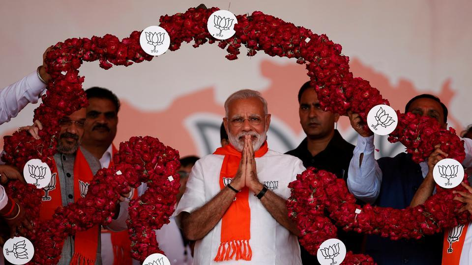 Prime Minister Narendra Modi is garlanded by supporters during a public rally at Bhaat village on the outskirts of Ahmedabad on October 16.