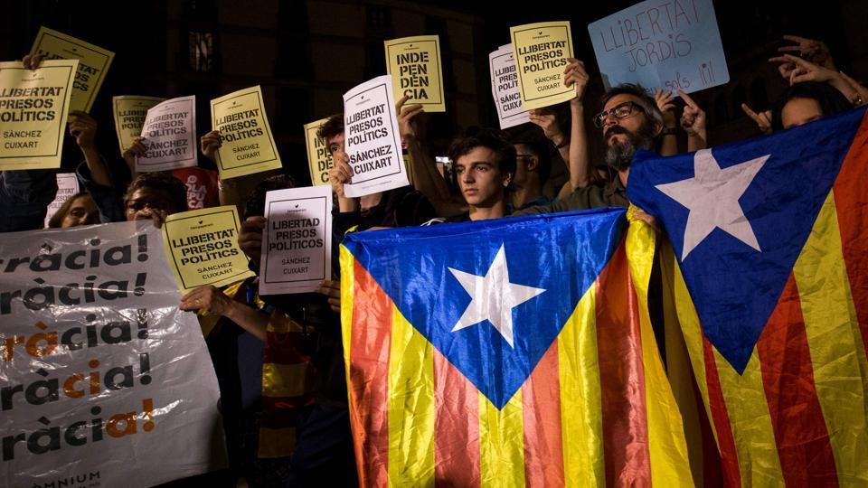 People hold Esteladas (Pro-independence Catalan flag) and papers reading in Catalan