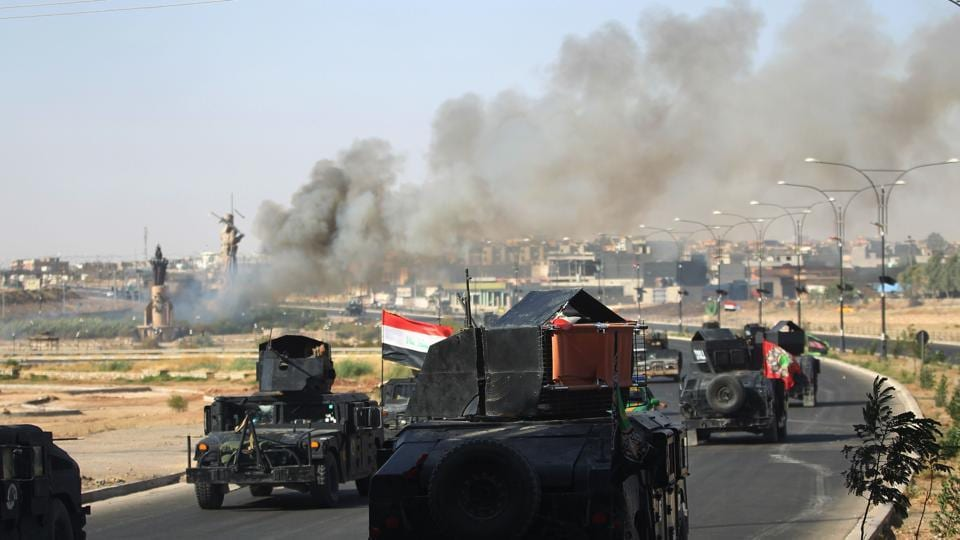 Smoke billows as Iraqi forces advance towards the centre of Kirkuk during an operation against Kurdish fighters on October 16.