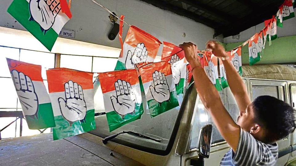 A Congress worker with party's election material in Shimla on Tuesday.
