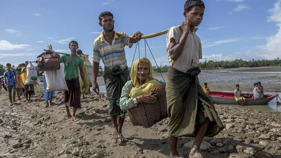 Rohingya Muslims, who crossed over from Myanmar into Bangladesh, carry an elderly woman in a basket and walk towards a refugee camp in Shah Porir Dwip, Bangladesh, September 14.
