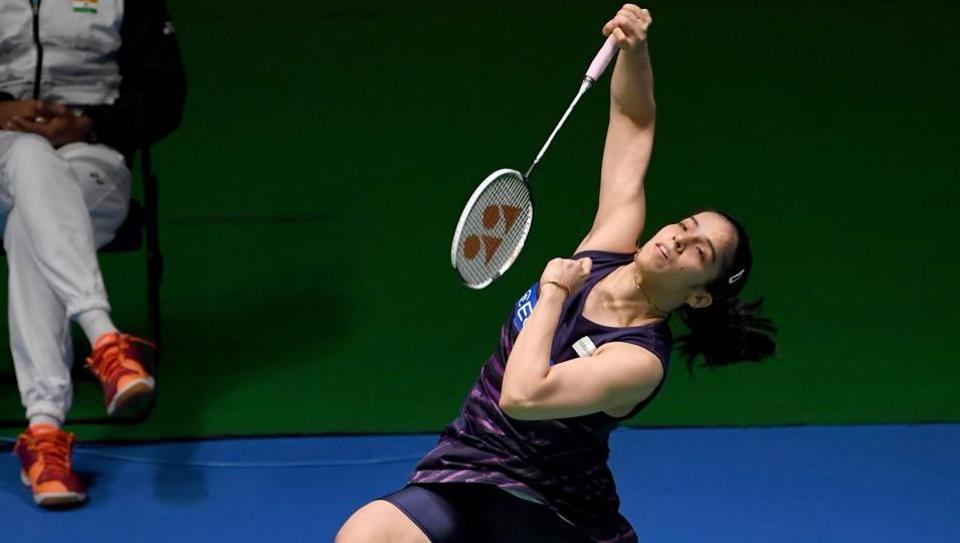 Saina Nehwal of India hits a return against Carolina Marin of Spain during their women's singles first round match at the Denmark Open badminton on Wednesday.