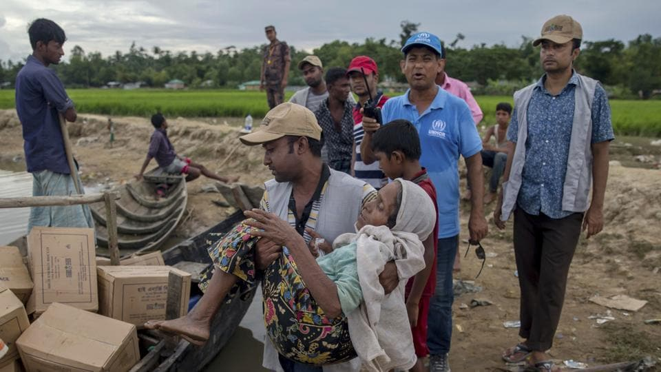 A Bangladeshi man carries a Rohingya Muslim woman Rajamma, who crossed over from Myanmar into Bangladesh, towards a boat filled with food aid for stranded refugees in Palong Khali, Bangladesh, Wednesday, Oct. 18, 2017.