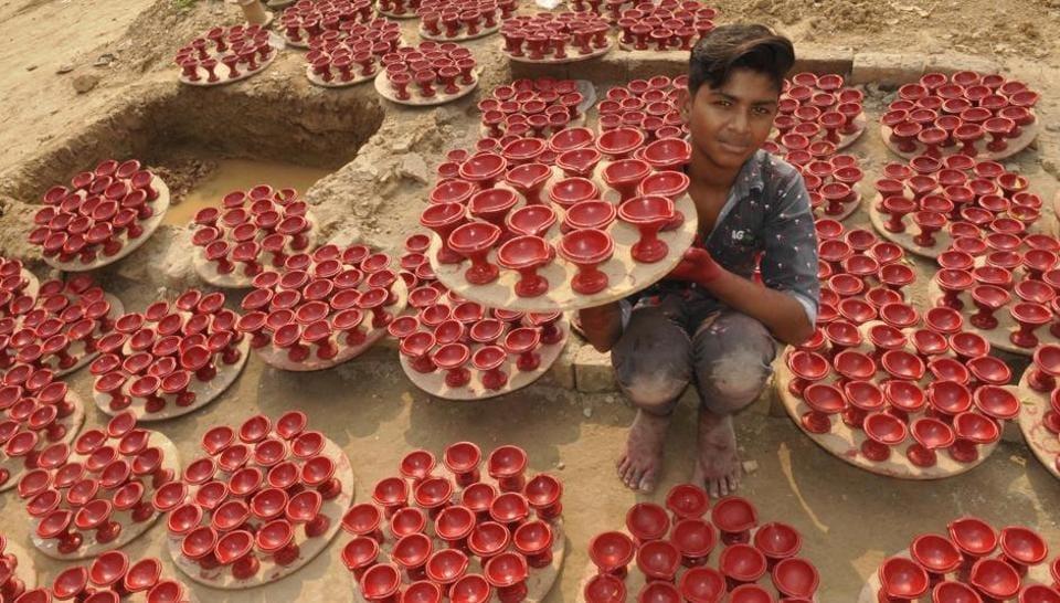 A boy showing diyas at Kumhar Colony in Maloya.